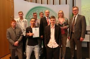 : Projektleiter Thomas Friedrich (4vr.) mit Jugendlichen aus dem Projekt (vordere Reihe) und Mitarbeitern (hintere Reihe) sowie Heinrich Deichmann (1vr.)